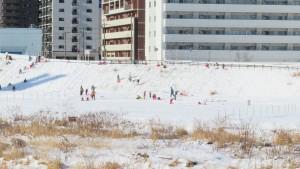 対岸で雪遊びをする子どもたち