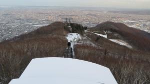 山頂からロープウェイ中腹駅と市街地を望む