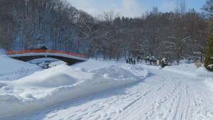 雪の園路と厚別川に架かる白帆橋